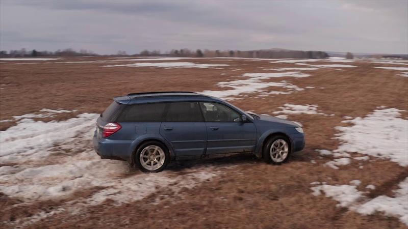 Subaru Outback на весеннем поле в полусликах BRIDGESTONE POTENZA ADRENALIN RE003