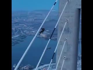 Альпинист удаляет наледь с моста на остров Русский